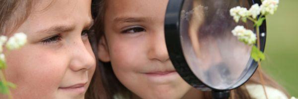 Bild på flickor och förstoringglas